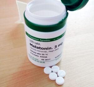Melatonin bottle and pills